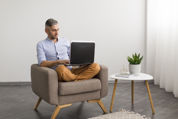 long-view-man-using-his-laptop-indoors_23-2148401423